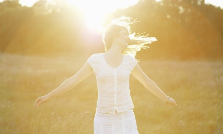 Woman with arms out stretched in front of sun.