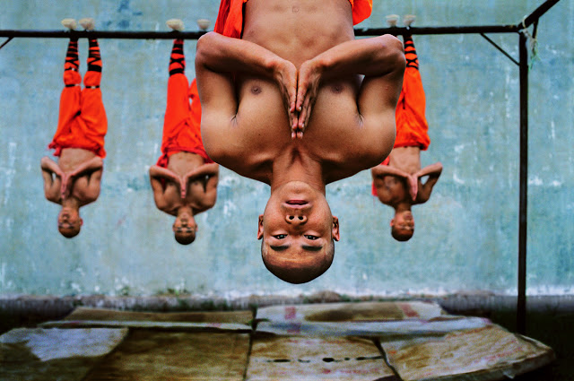 Shaolin monks training, Zhengzhou, China, 2004..The world famous Shaolin Monastery is known to many in the West for its association with martial arts, specifically Shaolin Kung Fu. McCurry pictures the monks suspended from a metal beam. The physical strength and dexterity displayed by the monks is incredible, although they exude a deep serenity...Phaidon..Iconic_Book..final print_UrbanArt'12.final print_MACRO'11